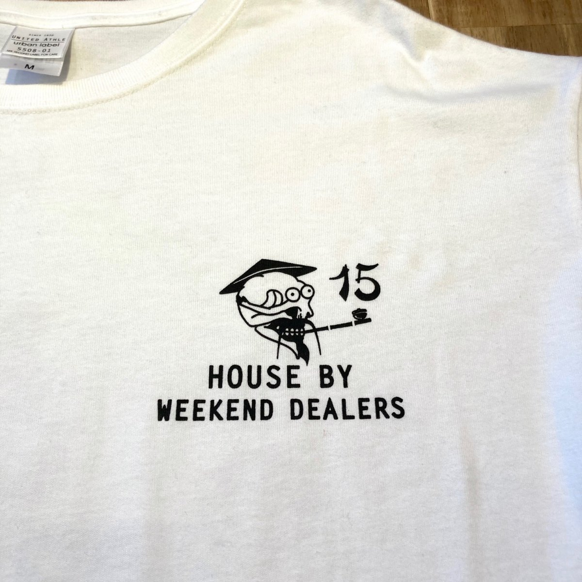 <img class='new_mark_img1' src='https://img.shop-pro.jp/img/new/icons3.gif' style='border:none;display:inline;margin:0px;padding:0px;width:auto;' />Black Weirdos × HOUSE by WEEKEND DEALERS 15th ANNIVERSARY Tee 【WHITE】