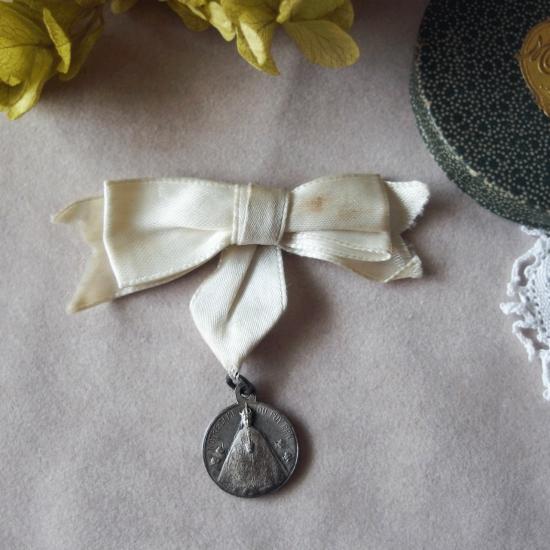 ノートルダム・ド・フランス 白いリボンとメダイのブローチ(紙製ケース付き)