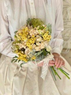 可憐なイエローとホワイトの小花にグリーンを加えた造花とドライフラワーのmixクラッチブーケ。