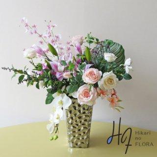 高級造花アレンジメント【ムシカ】人気のカラテア・オルビフォリア(葉物)を入れて、スタイリッシュ感と、胡蝶蘭・オンシジュームでエレガント感を同居させました。
