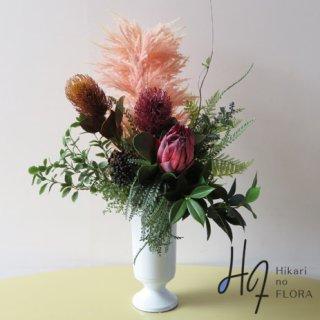 高級造花アレンジメント【ローザ】花言葉「華やかな期待・王者の風格」のキングプロテアと、バンクシア。アートな高級造花アレンジメントです。照明を抑えた空間のインテリアとしても。