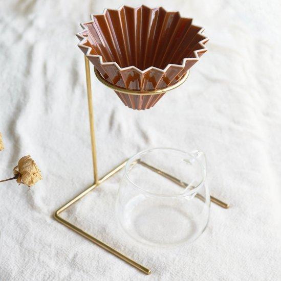 こだわりの道具で淹れるコーヒーは、飲む前の時間さえも楽しい。    飲む前からコーヒーを楽しく。  軽量で扱いやすく、アウトドアシーンでも活躍。  シンプルなデザインはドリッパーを引き立ててくれます。  円形部分にオリガミドリッパー等を直接置いてのドリップも可能です。    独特な質感や深みのある光沢が雰囲気を醸し出す真鍮。  ヴィンテージ感のあるブラスは、コーヒーを淹れる時間から雰囲気を演出してくれます。  使い込むうちに変色による風合いの変化も真鍮の素材ならではの特徴です。    年月の経過とともに、自分だけのアンティークを感じられるドリッパースタンド。  普段のコーヒータイムにはもちろん、お友達を呼んでのパーティーシーンにもおすすめ。    もちろんV60 ドリップスケールも設置可能◎  いつもの毎日を、少し贅沢に。  【商品について】 生産地:インド サイズ:W13.5×D13×H18cm  素材:BRASS ブランド:Horn Please