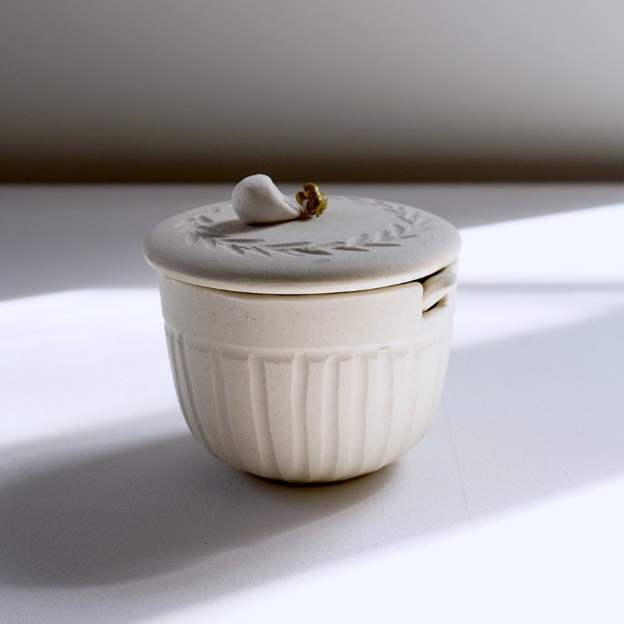 white sugarpot with spoon